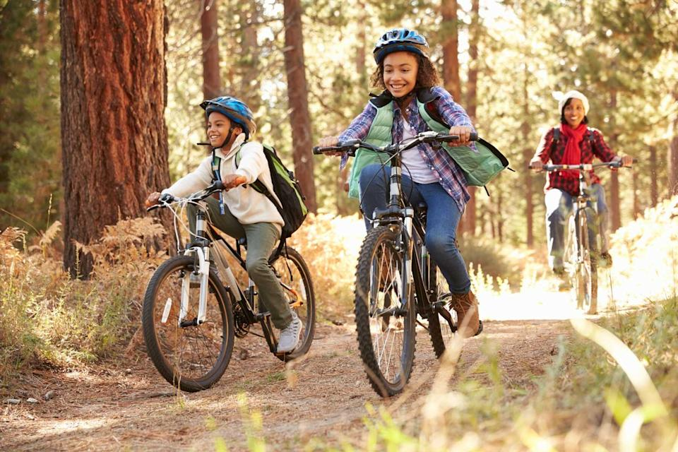 Two kids and a mom cycling on a path in the forest, to represent a tour with Thomson Family Adventures, voted one of the world's best Tour Operators