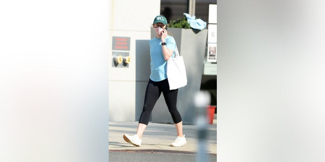 The former first daughter, who is wearing a mask talks on her cellphone as she heads to the gym.
